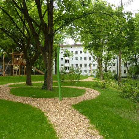 Auf diesem Bild sieht man ein weißes Mehrfamilienhaus im Hintergrund von dem ein Holzspähneweg zu einem Spielplatz führt. Der Spielplatz hat ein Klettergerüst mit Rutsche. Die Bäume und die Wiese sind grün.