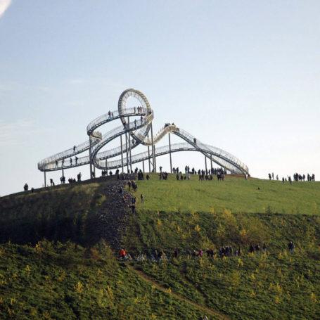 Zu sehen ist das Tiger and Turtle in Duisburg. Es ist wie eine Art Achterbahn aufgebaut, nur kann man auf Treppen bis nach oben laufen. Auf dem Bild sieht man auch mehrere Personen.