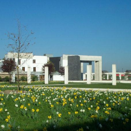 Zu sehen ist ein weißes Gebäude im Garten der Erinnerung. Im Vordergrund sind Narzissen in gelb und weiß zu sehen.