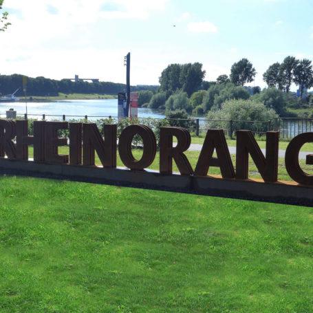 """Auf dem Bild sieht man den Schriftzug """"Rheinorange"""" auf einer kleinen Mauer. Vor dem ersten Buchstaben ist ein Pfeil nach links zu sehen, der als Wegweiser dient. Im Hintergrund sieht man ein Stück vom Rhein und Bäume."""