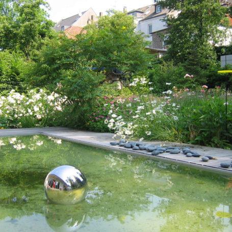 Auf diesem Bild sieht man einen kleinen Teich mit einer Silbernen Kugel im Wasser. Rund herum um den Teich, ist eine Holzverkleidung und Blumenbeete mit vermutlich Wildblumen. Im Hintergrund sieht man Häuser.