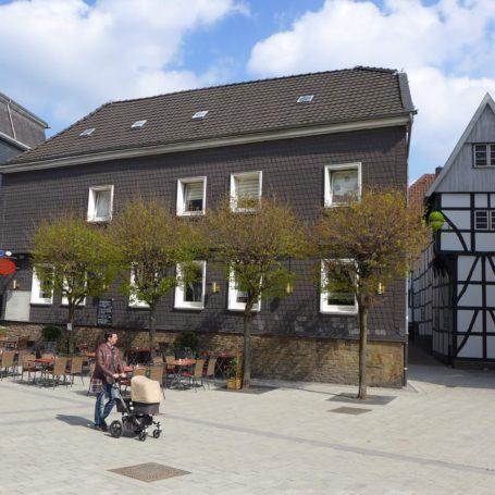 Man sieht die Straße vor dem Bügeleisenhaus in Hattingen. Ein Mann läuft mit Kinderwagen an einem bestuhlten Platz vorbei.