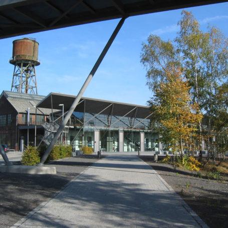 Auf diesem Bild sieht man die Jahrhunderthalle in Bochum. Im Hintergrund steht ein großer Wasserturm. Links von der Halle ist ein Parkplatz auf dem ein schwarzer Kombi und ein rotes Auto stehen. Vor der Halle ist ein gepflasterter Weg und ein paar Bäume zu sehen. Quer durch das Bild verläuft waagerecht eine Brücke.