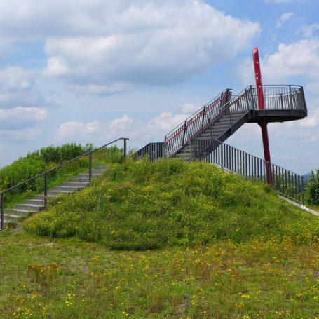 Auf diesem Bild sieht man den Aussichtspunkt der Halde. Sie besteht aus einer Plattform und einer Treppe die zu dieser führt. Rundherum ist es begrünt durch Bäume und Wiesen mit Blumen. Vor der Treppe zur Plattform steht ein Fahrrad.