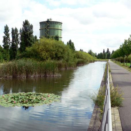 Zu sehen ist eine Art Biotop. Auf der linken Seite sieht man eine Art Teich mit einem Gasometer. Rechts ist ein Weg zum gehen.