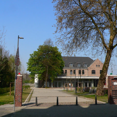 Auf diesem Bild sieht man die alte Feuerwache und den Eingang samt Weg zu dem Gebäude. Rechts im Bild sieht man geparkte Autos und einen größeren Baum der leicht nach rechts neigt. Links auf der Grünfläche sind ein paar schmale Bäume mit Holzverkleidung gepflanzt und man sieht ein Straßenschild.