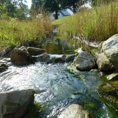 Auf diesem Bild sieht man wie Wasser vom Bach von der oberen Empore etwas runter läuft auf die tiefergelegene. Im Wasser sind große Steine über die das Wasser ebenfalls läuft. Im Hintergrund sieht man ein weißes Haus und Wiese mit etwas höheren Gräsern.