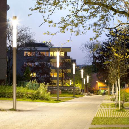 Auf diesem Bild sieht man einen Weg der gepflastert ist. Links sieht man Wohnhäuser mit mehreren Etagen und Laternen die leuchten. Rechts im Bild sieht man Bänke zum sitzen und Bäume.