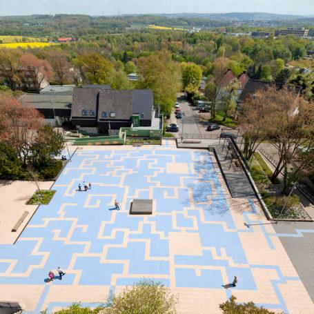 Auf diesem Bild sieht man den Hufelandplatz in die Blickrichtung Osten. Das Muster des Platzes ist wie ein Labyrinth aufgebaut und fasst die Farben beige und hellblau. In der Mitte des Platzes ist eine Holzplatte die quadratisch ist. Links vom Platz ist eine Tischtennisplatte aufgebaut und Holzbänke zum sitzen. Oben im Bild sieht man viele Bäume, ein paar Häuser und eine Fabrik o.ä. Rechts im Bild befindet sich eine Rollstuhlrampe.