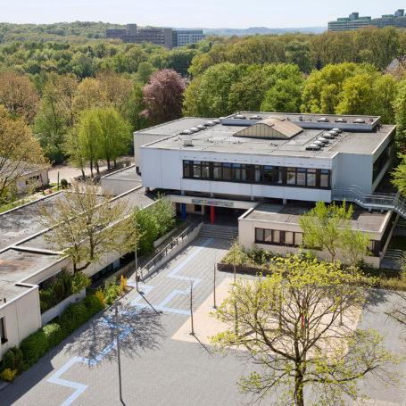 Auf diesem Bild sieht man eine Luftaufnahme der Hufelandschule. Unten rechts im Bild sieht man ein kleines Beet mit einem Baum. Auf der linken Seite schlängelt sich eine blaue Linie bis zum Eingang des Schulgebäudes. Am Gebäude selbst sind Büsche und Bäume gepflanzt. Etwas weiter im Hintergrund sieht man einige Hochhäuser.
