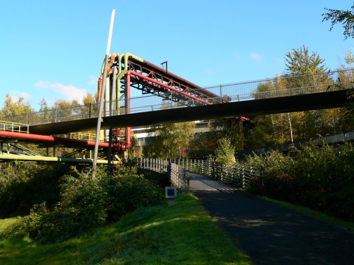 Man sieht eine Rohrleitung die unter eine Brücke hindurch verläuft. Die Rohre haben alle verschiedene Farben.