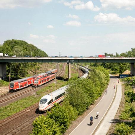 Auf diesem Bild sieht man die Bahnstrecke auf der sich ein ICE und zwei DB-Regio-Züge befinden. Rechts daneben ist die Fahrrad-Trasse mit einigen Radfahrern. Über der Bahnstrecke verläuft eine Brücke auf der mehrere Autos stehen, vermutlich eine Autobahn. Zwischen Trasse und Schienen sind Büsche und Bäume gepflanzt.