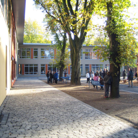 Auf diesem Bild sieht man einen Schulhof, vermutlich von einer Grundschule da rechts im Bild ein Klettergerüst vorhanden ist. Man sieht ein paar Schüler auf dem Schulhof und ein paar Erwachsene.