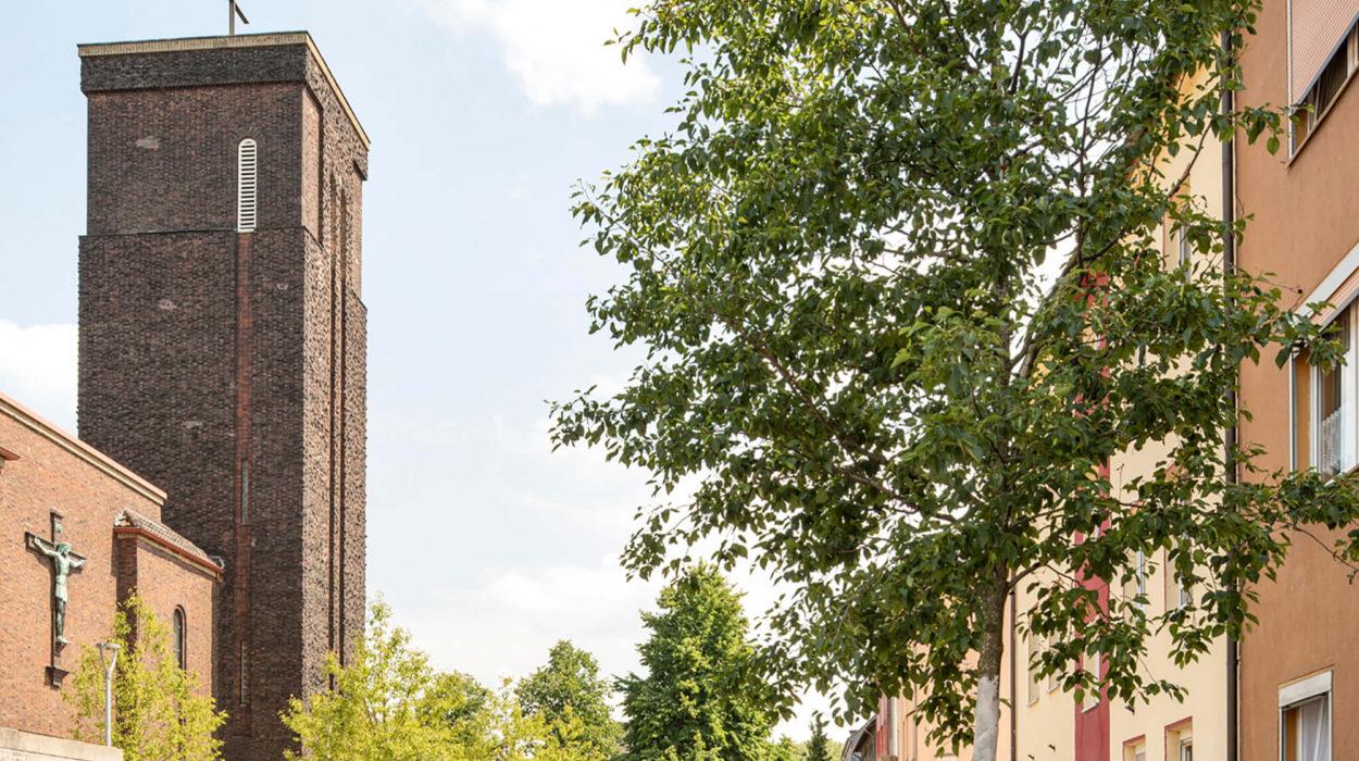Auf diesem Bild sieht man eine Spielstraße mit parkenden Autos. Die Blickrichtung ist auf eine Kirche die links steht. Sie ist eine eckige Kirche die aussieht wie ein Turm. Auf dem Dach des Kirchturms ist ein Kreuz befestigt. Im Vordergrund des Bildes steht ein Baum.
